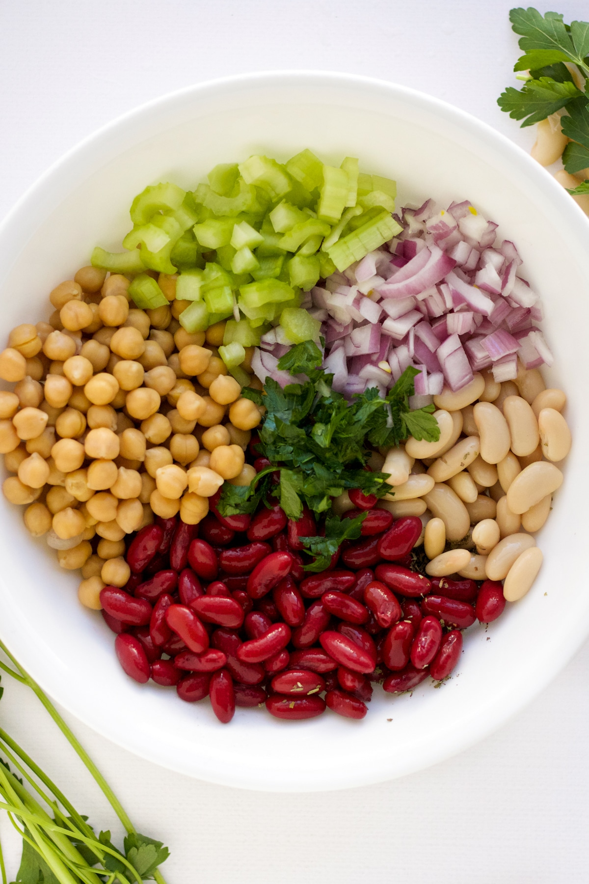 kidney, garbanzo, and cannelini beans in a white bowl with chopped celery and red onion and parsley