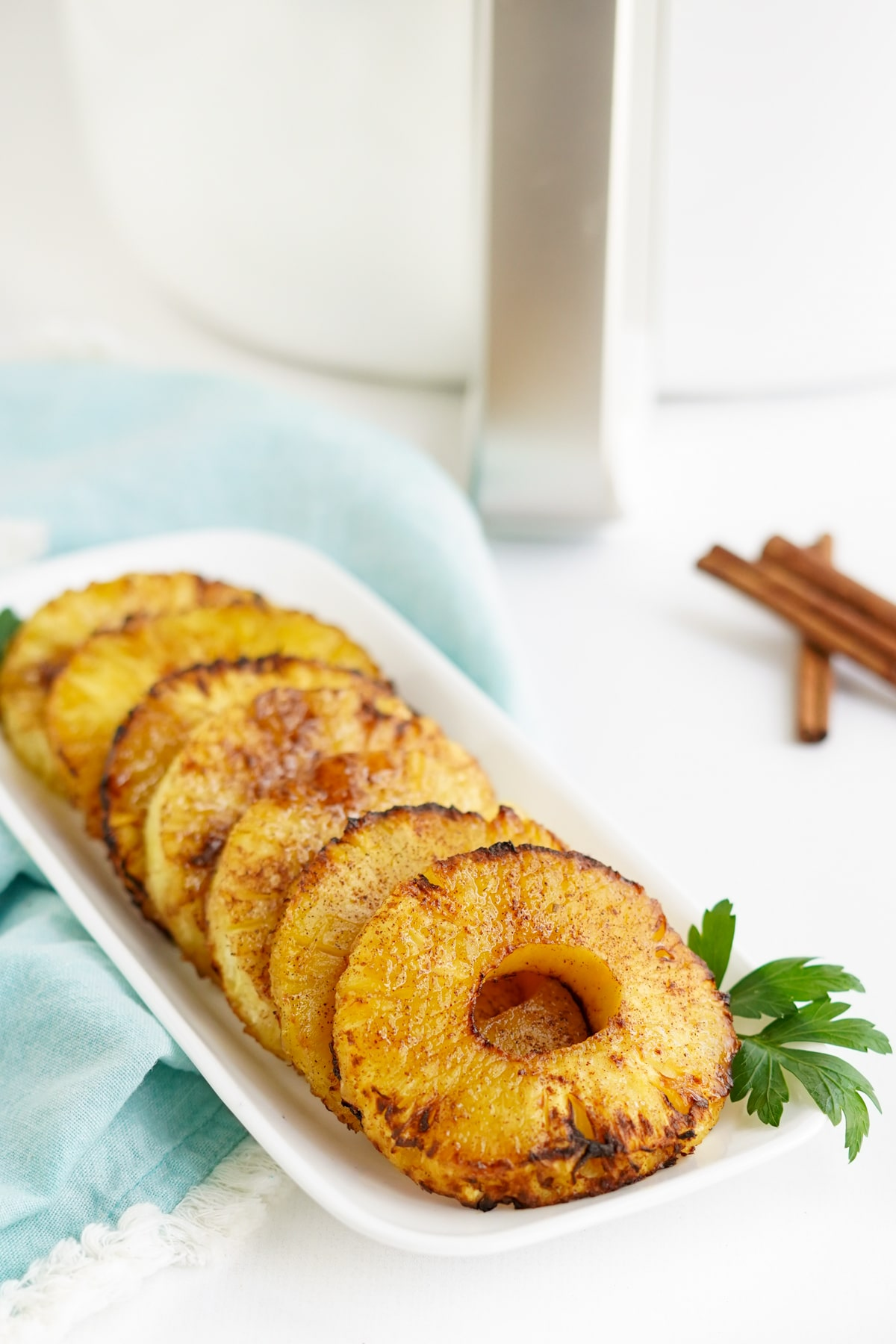 air fryer pineapple on a white platter with parsley garnish
