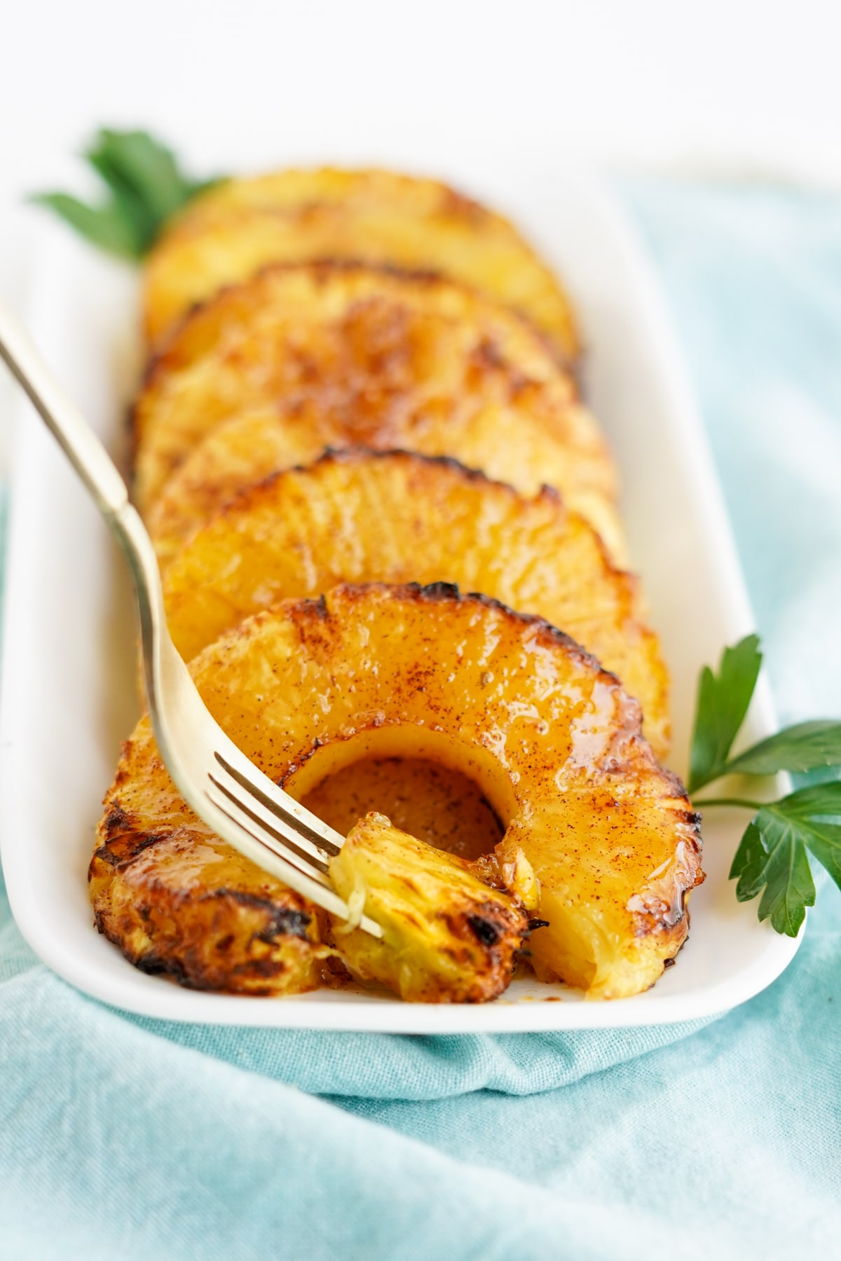 caramelized pineapple rings on white platter with fork