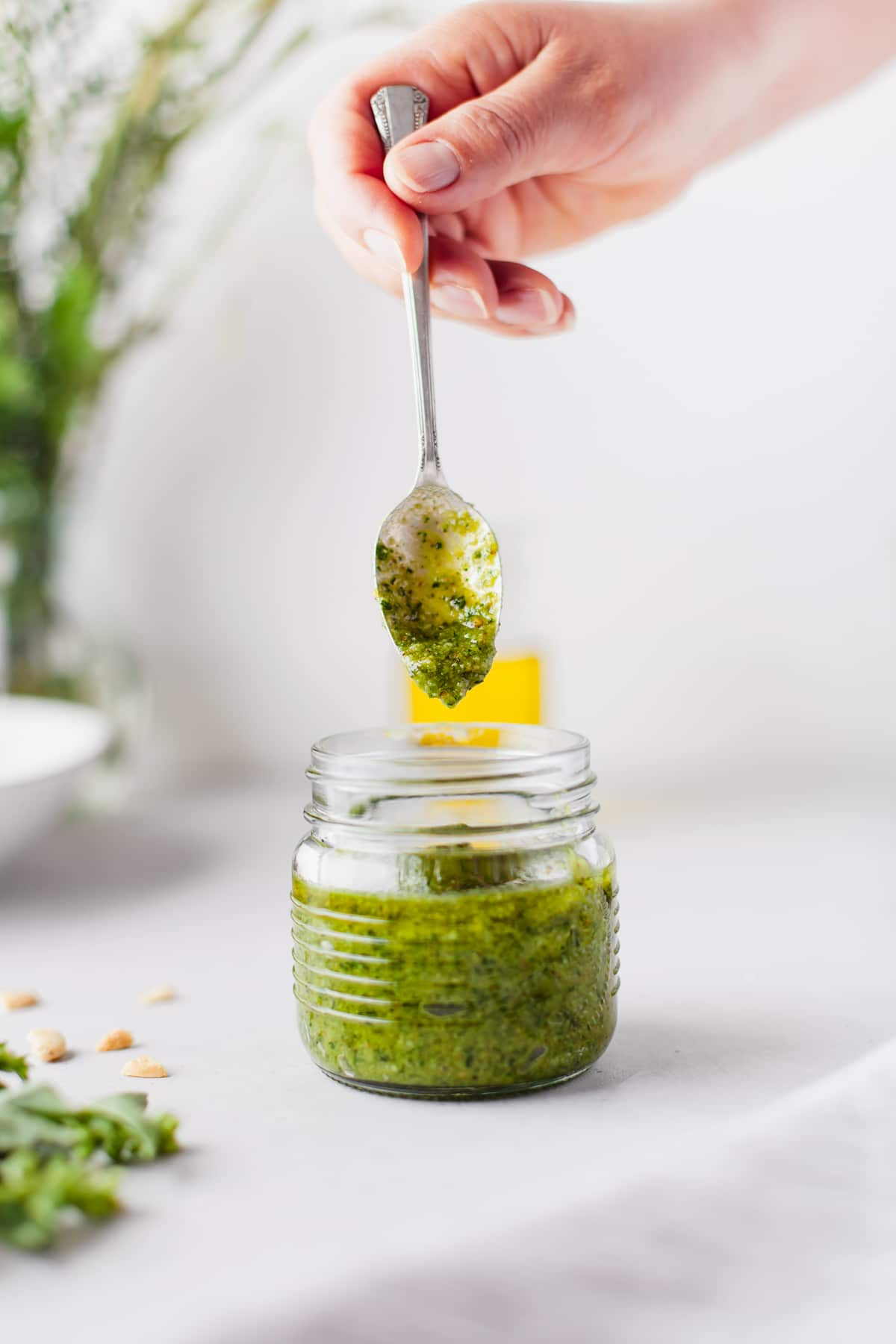 hand with spoon in a glass jar of pesto