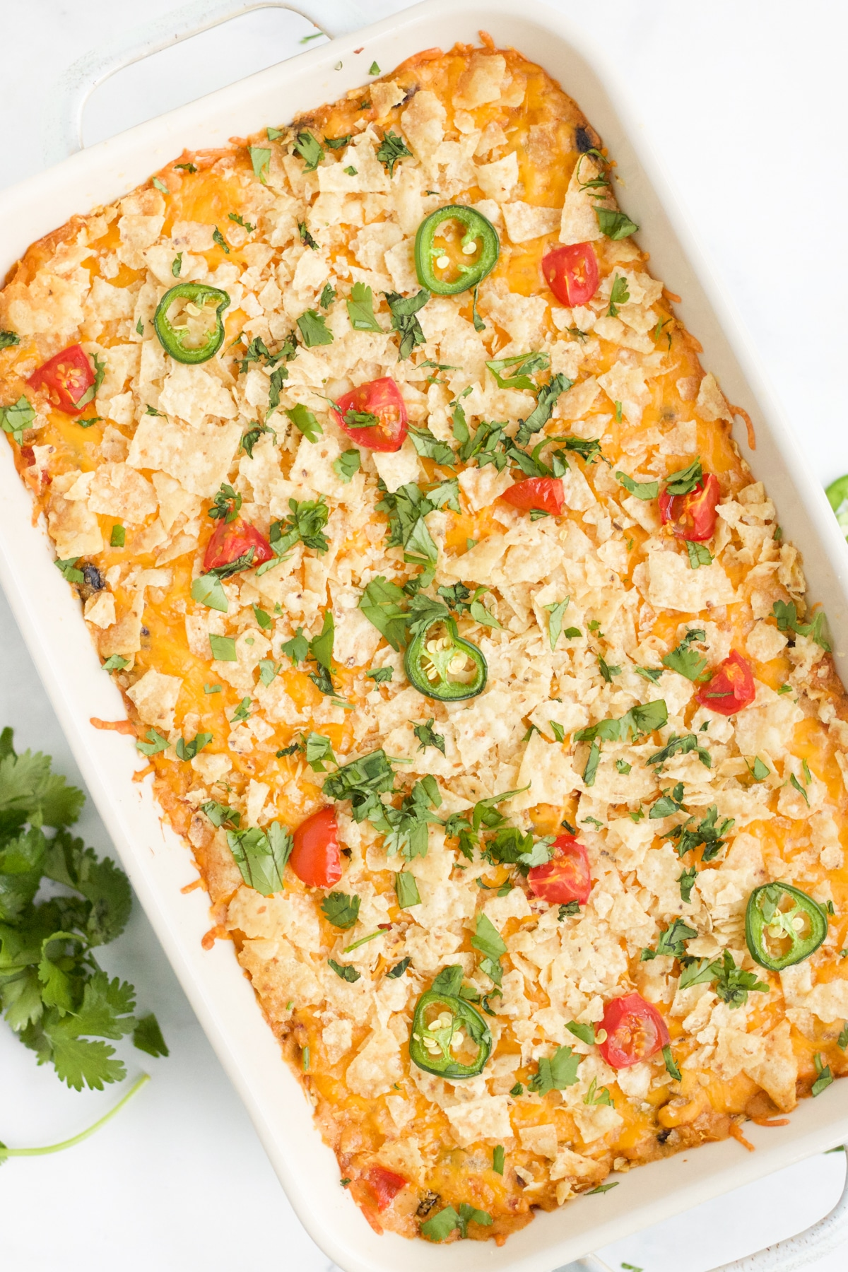 Overhead image of chicken taco casserole bake. The casserole is garnished with herbs, tomatoes and jalapeños.
