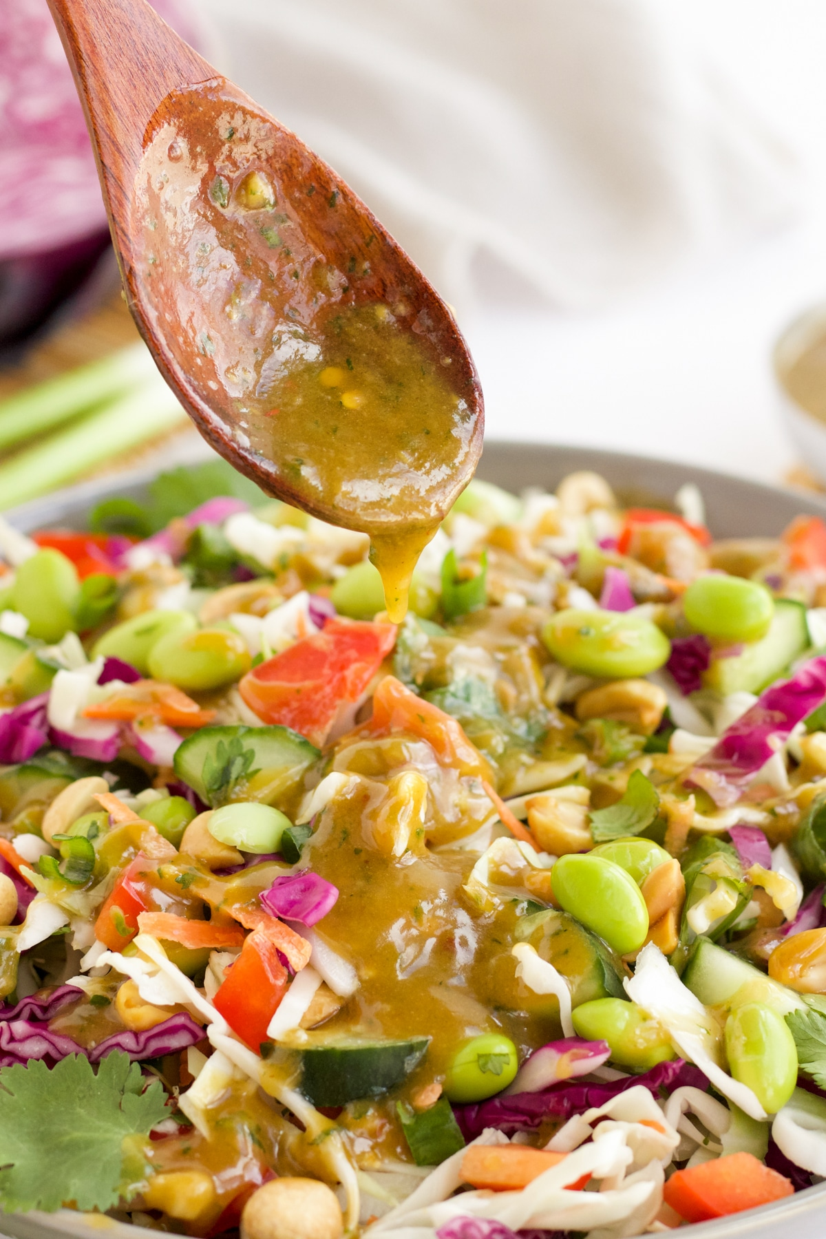 Creamy peanut dressing being drizzled onto a thai salad.