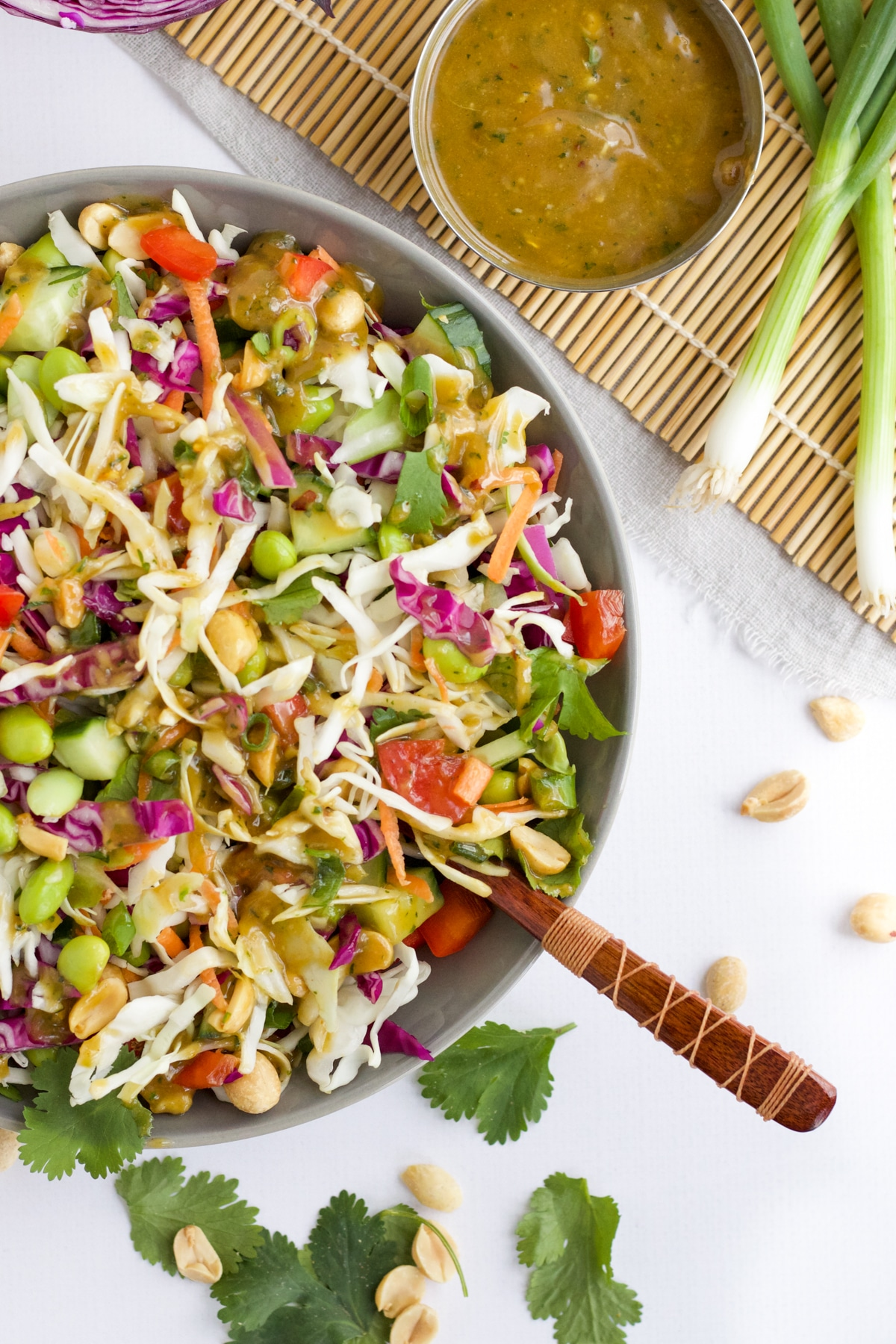 An overhead image of thai-inspired salad in a grey bowl with a side of dressing