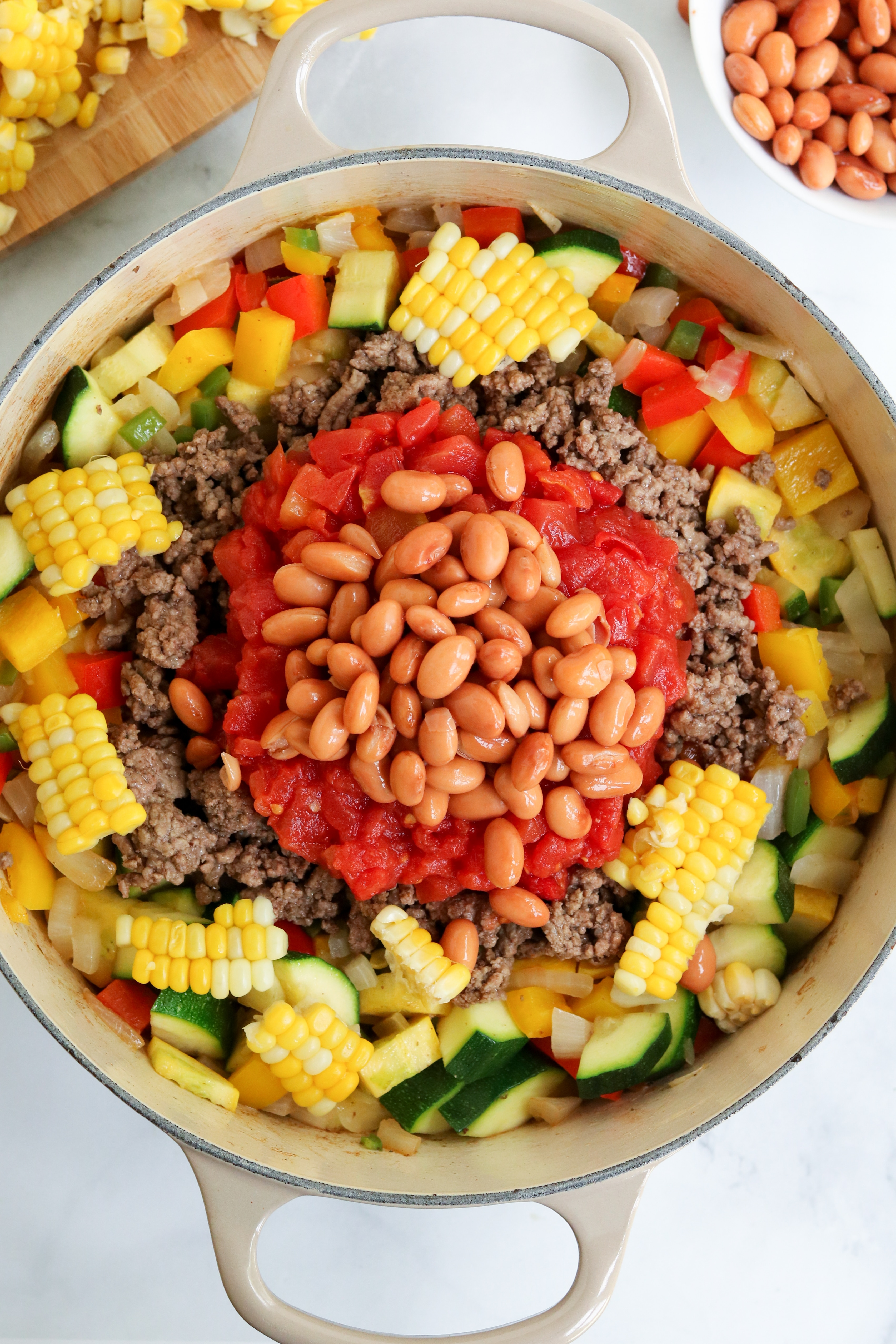fresh farm veggies, ground beef, tomatoes, and beans in a dutch oven