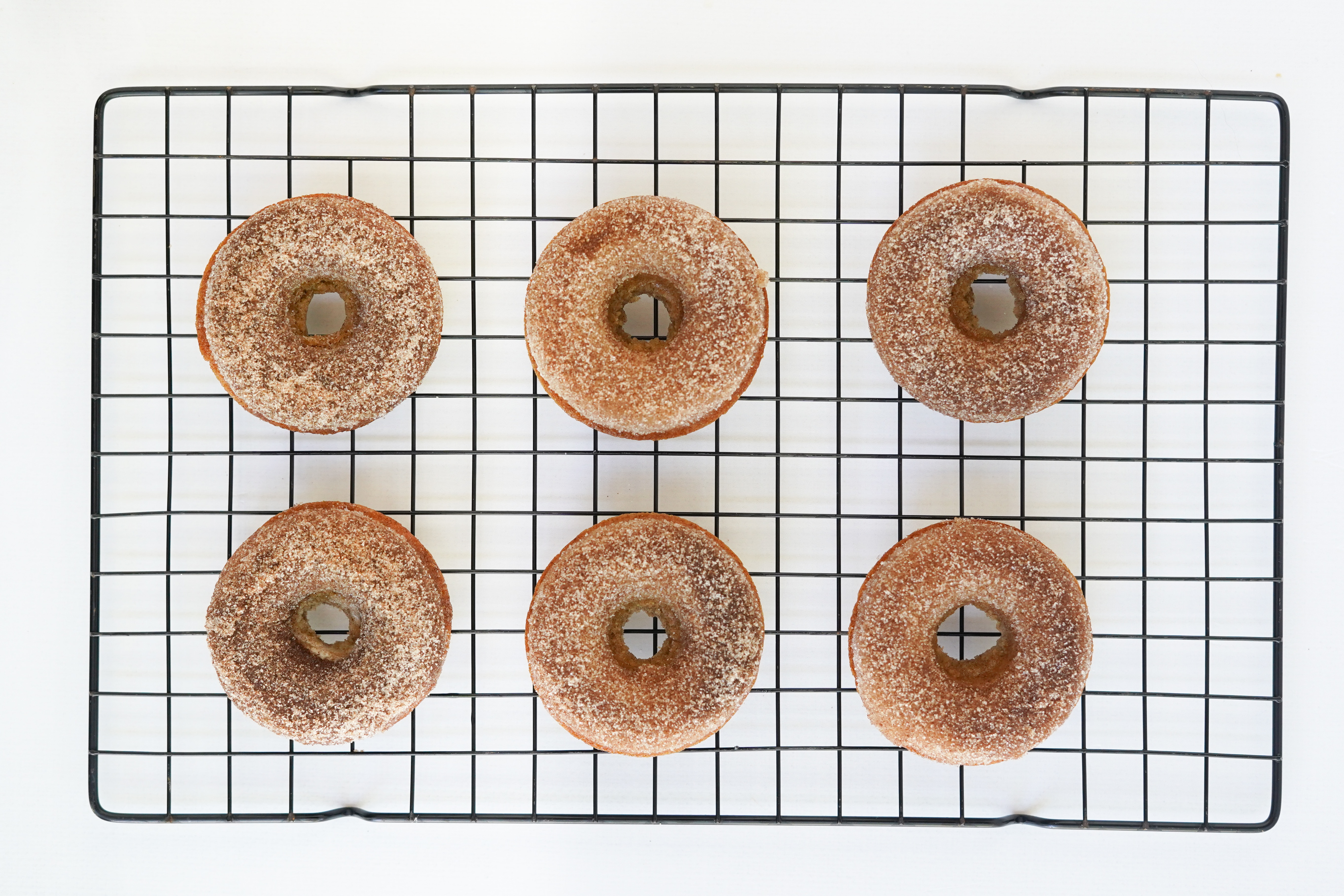 apple cider doughnuts on cooling rack sprinkled with cinnamon and sugar
