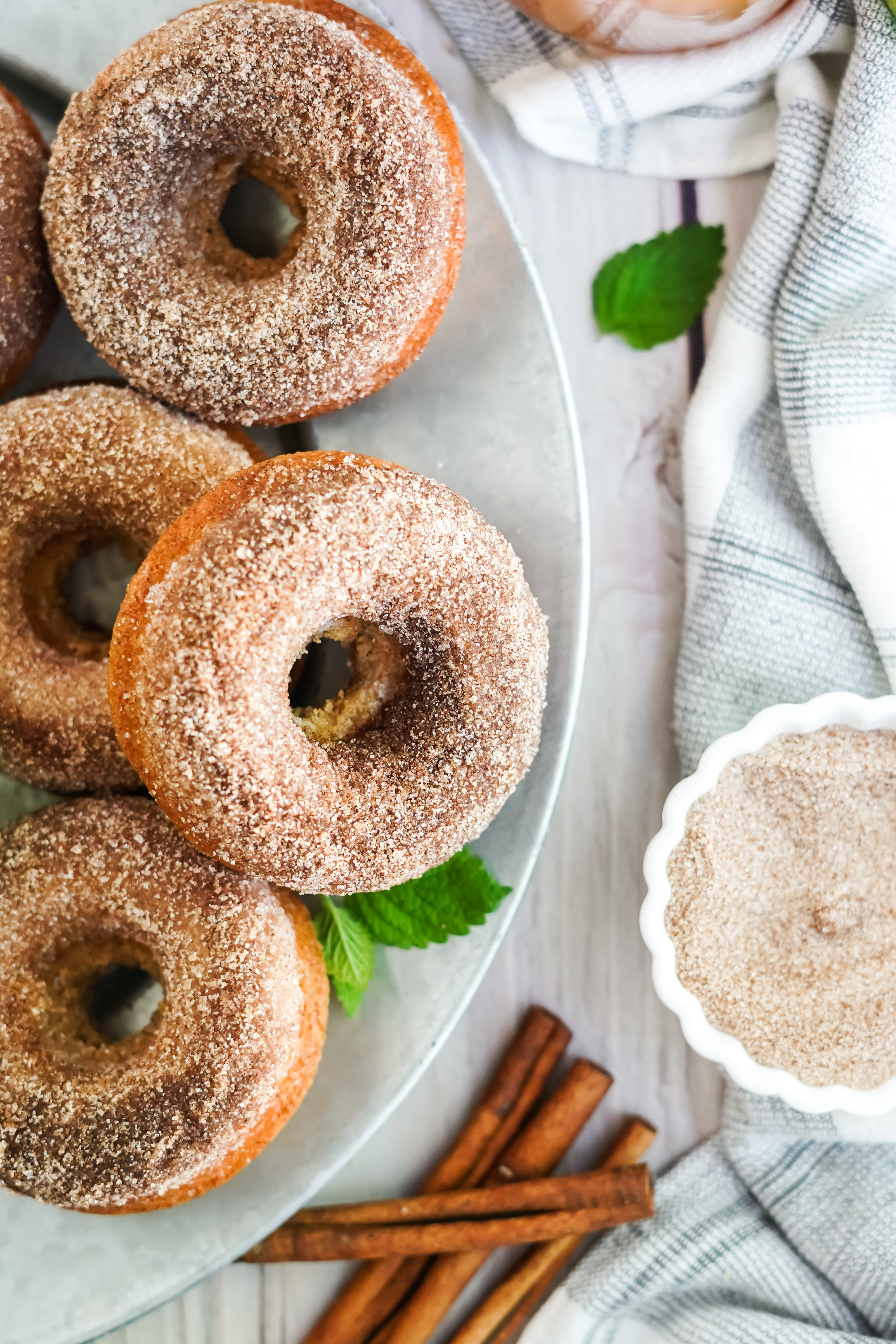 plate of apple cider doughnuts with bowl of cinnamon and sugar