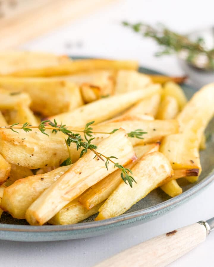 plate of parsnips with fork and thyme garnish
