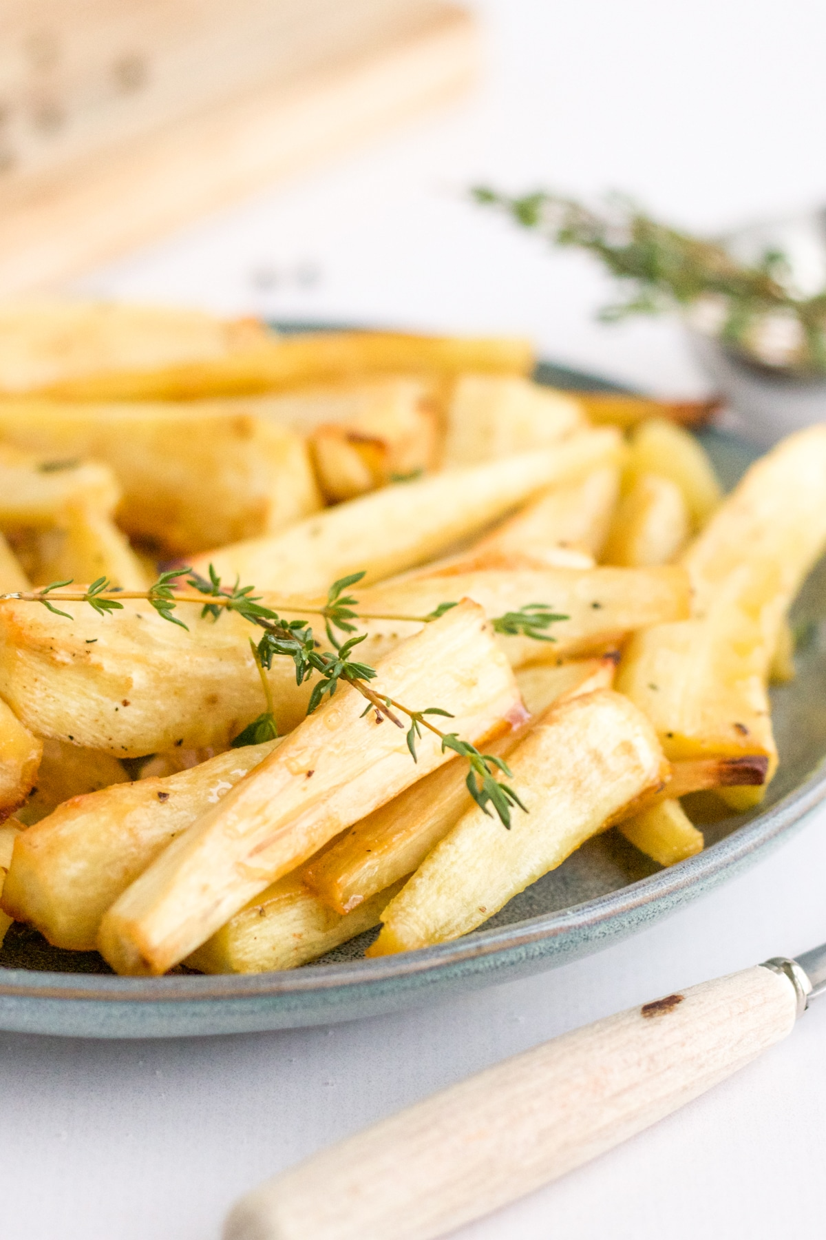 plate of roasted parsnips with fork and thyme garnish