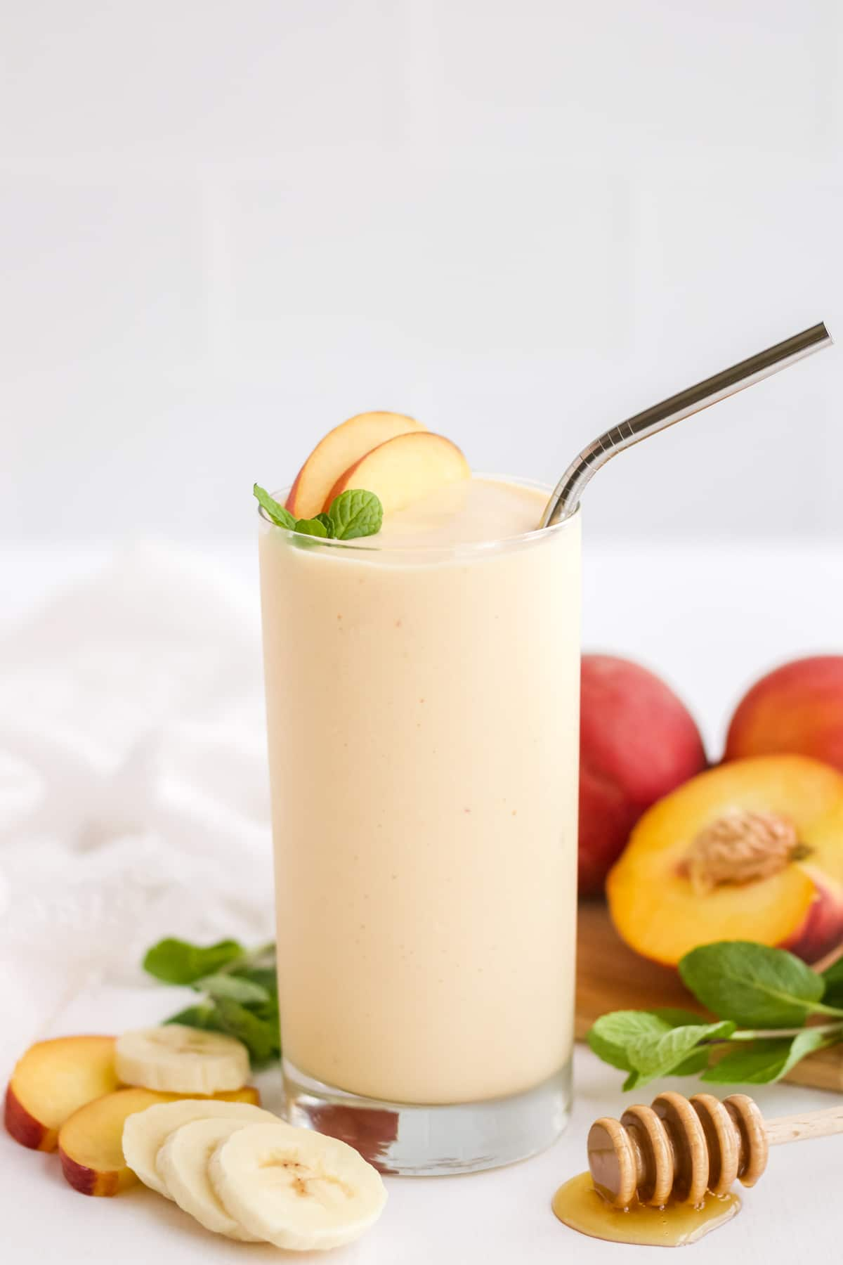 A single glass of peach smoothie garnished with peach slices and a sprig of mint.