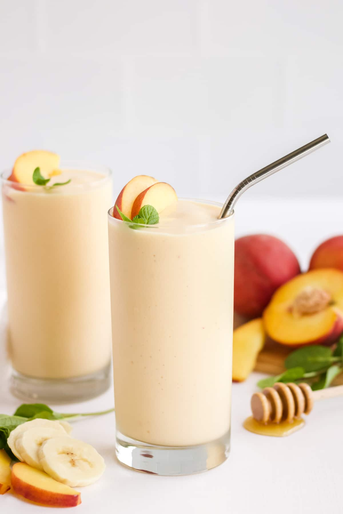 Two glasses of a peach smoothie with peaches and honey in the background
